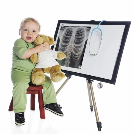 An adorable baby boy in green scrubs hugging his toy bear as he sits by an easle displaying a human chest x-ray   On a white background  photo