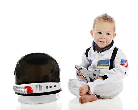An adorable baby happily playing with a toy space shuttle while wearing his astronaut uniform and sitting by his space helmet   On a white background  photo