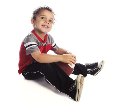 A adorable preschooler happily looking up as he sits with his football.  On a white background. Stock Photo