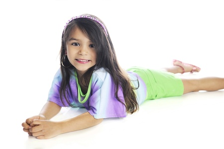 sprawled: A beautiful elementary girl happily looking at the viewer as she lays on her belly in casual, summer clothes.  On a white background.