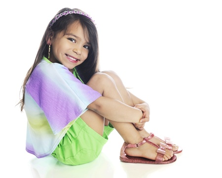 sandles: A beautiful, young elementary girl happily looking at the viewer as she sits in her casual summer clothes.  On a white background.