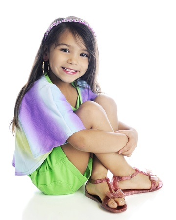 sandles: A beautiful young elementary girl with long, brown hair sitting with her arms wrapped around her legs.  On a white background. Stock Photo