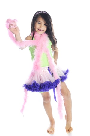 boas: A beautiful barefoot elementary girl in a fluffy pink and purple tutu and wrapped in pink boas.  On a white back background.