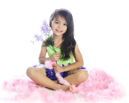 boas: Una bella ragazza elementare felicemente seduta con un piccolo bouquet, mentre circondato da soffici boa rosa. Su uno sfondo bianco.