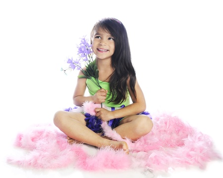 A beautiful elementary girl happily sitting with a small bouquet while surrounded by fluffy pink boas.  On a white background. Stock fotó