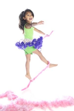 boas: Una bella ragazza elementare scalzi felicemente saltando da e con soffici boa rosa. Su uno sfondo bianco.
