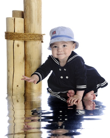 sailor girl: An adorable barefoot baby reaching for the water in her sailor girl outfit.  On a white background.