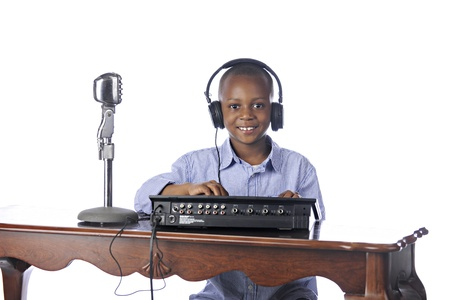 dj boy: A happy elementary boy sitting at a table playing DJ with earphones on, a microphone nearby while working on a sythesizer.  On a white background.