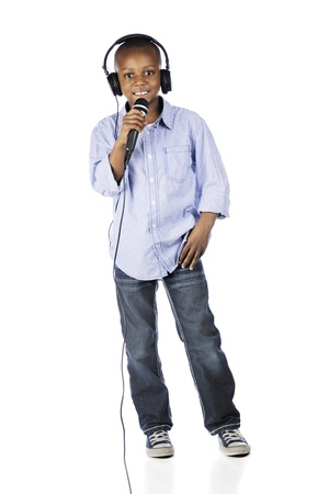 A handsome elementary boy speaking into a microphone while wearing a DJs headset.  On a white background.
