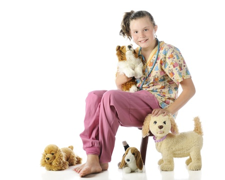A pretty elementary veterinarian surrounded by her stuffed pets.  On a white background. photo