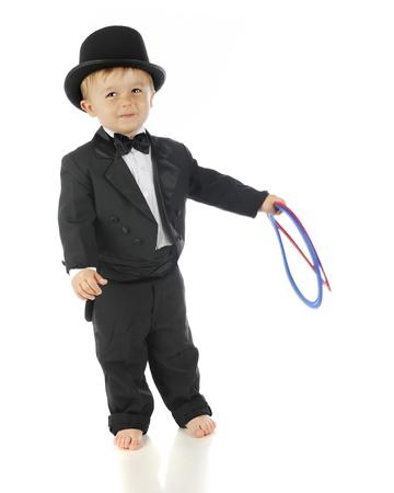 tophat: Un adorabile, bambino a piedi nudi sorridente nel suo smoking e tophat. Ha in mano due anelli flessibili. Su uno sfondo bianco. Archivio Fotografico