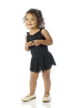 An adorable toddler happy in her black dance dress with tutu and too-big shoes.  On a white background.