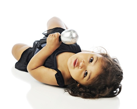 An adorable toddler looking back at the viewer as she lays on the floor in her dance dress while holding a large microphone.  On a white background. photo