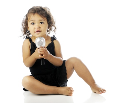 An adorable toddler singing with a microphone while sitting on the floor in her black dance dress on a white background. photo