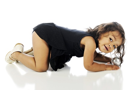 An adorable toddler looking the the viewer while on hands and knees in her dance dress.  On a white background.