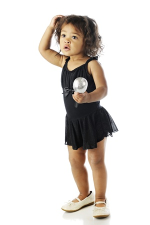 An adorable little performer holding a microphone while wonderingly standing in her dance dress and oversized shoes.  On a white background. photo