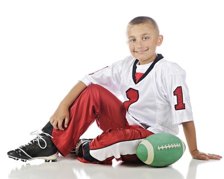 handome: A happy, handome elementary boy relaxed in his sport uniform and football.  On a white background.