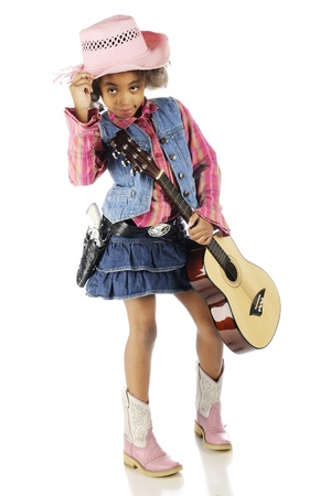 tipping: An elementary-aged cowgirl tipping her hat with one hand as she holds her guitar in the other.  On a white background.