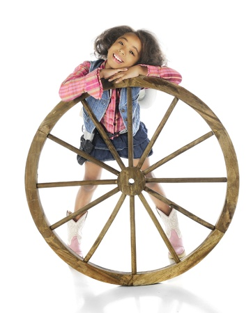 A happy elementary cowgirl happily relaxing her head on a rustic wagon wheel.  On a white background. photo