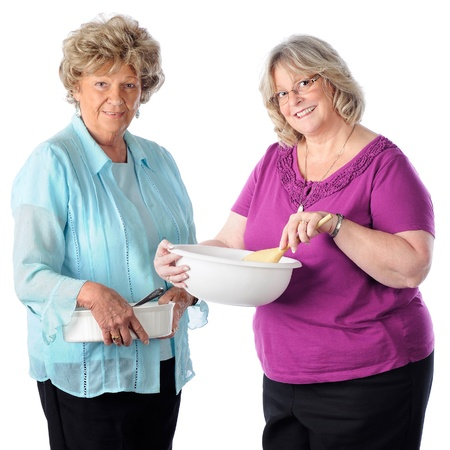 Two senior women happily posed with their baking dish and mixing bowl.  On a white backgound.