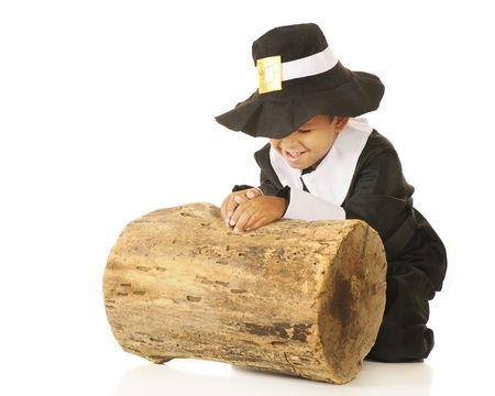 An adorable preschooler in a pilgrim outfit praying, giving thanks, by an old log. Stock Photo