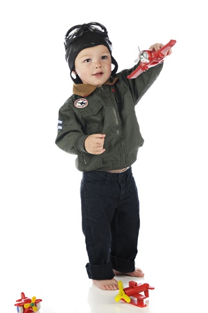 An adorable toddler happily hand flying his a toy airplane while wearing his old fashioned pilots outfit.  On a white background.