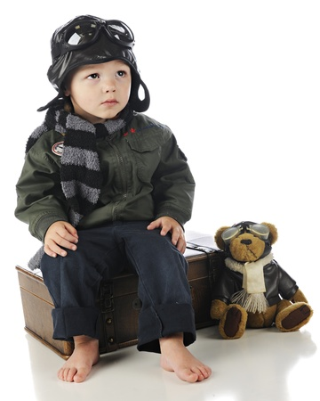 An adorable toddler sitting on his suitcase while watching for an airplane in his old-time pilot's outfit, his pilot teddy bear by his side.  On a white background. photo