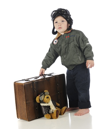 An adorable toddler in his old-time pilot outfit picking up his suitcase.  On a white background. photo