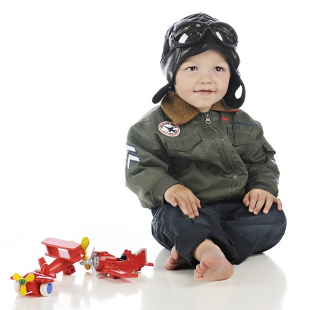 An adorable toddler happily sitting by his toy propeller planes in his old-time pilot outfit.  On a white background. photo