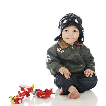 An adorable toddler in an old-time pilots out fit with toy, wooden propeller planes by his side.  On a white background. photo