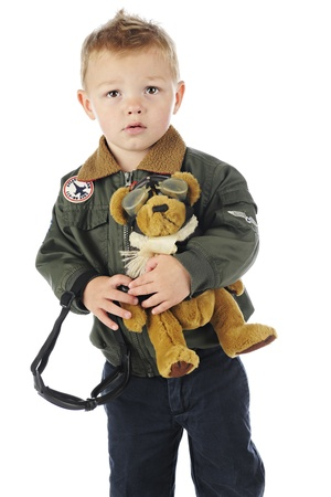 A worried preschool old-time pilot carrying his goggles and a stuffed pilot-bear.  On a white background.   photo