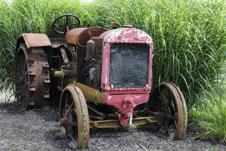 Close-up image of a runsty old tractor sitting in a bed of gravel and with a backdrop of tall grass. 版權商用圖片 - 22172712