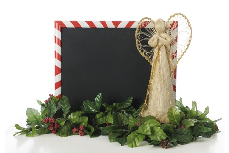 A candy-cane striped frame around a black board for your text.  An angel shape stands it beside in prayer with holly around them both.  On a white background. photo