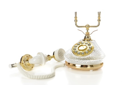 earpiece: A high-keyed image of a fancy, French-style cradle phone with the mouth-ear piece laying beside the phones body.  Ona white background.