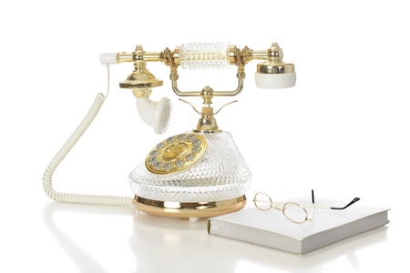 earpiece: A high key image of gold glasses on a closed book by a fancy French-style phone.  On a white background.