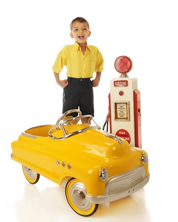 An adorable preschooler standing by a model old gas pump with his yellow pedal car.  On a white background. photo