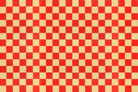 A red check pattern painted on a blond wood board.