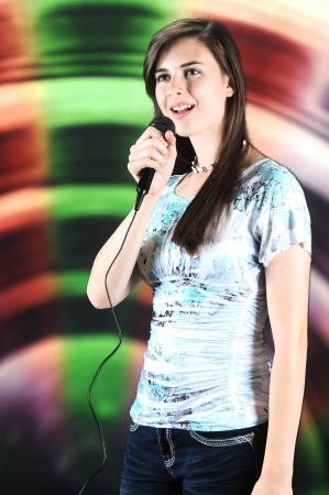 soloist: A vertical image of a beautiful teen soloist happily singing into a microphone.