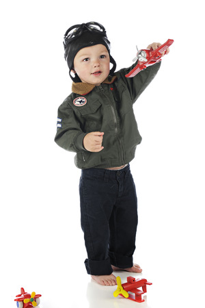 An adorable toddler happily hand flying his a toy airplane while wearing his old fashioned pilots outfit.  On a white background. photo