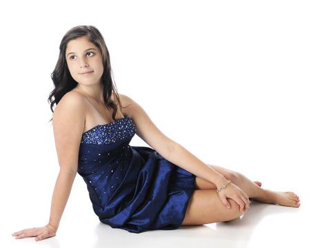 Een beatuiful jonge tiener zitten op blote voeten in haar strapless blauwe prom dress. Op een witte achtergrond.