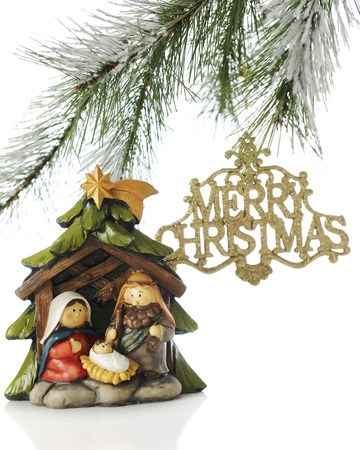 A small nativity scene under the boughs of a Christmas tree with a sparkly gold Merry Christmas ornament hanging nearby.  On a white background.