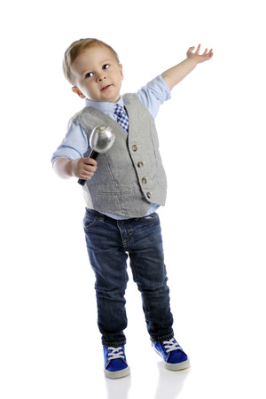 child singing: An adorable 2-year-old boy giving his grand finale with a microphone in one hand and his other extended.  On a white background.