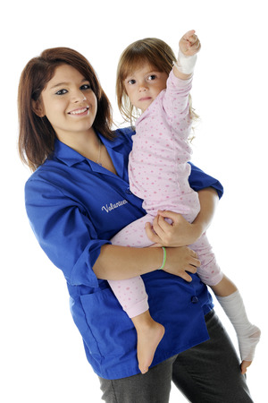 volunteer point: A pretty young hospital volunteer happily holding an injured preschooler.  The child has bandages wrapped around her wrist, leg and foot, as well as a bandaid on her head.  On a white background.