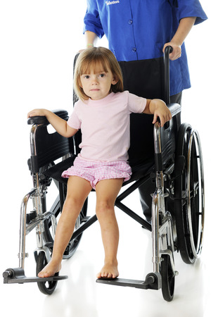 an adorable preschooler riding in a big wheelchair that's being pushed by a volunteer.  On a white background. Stock Photo - 22450215