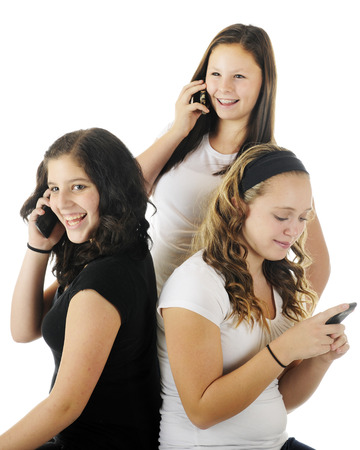 Three young teens talking and laughing on their communication devices.  On a white background.  Focus on girl in black. photo