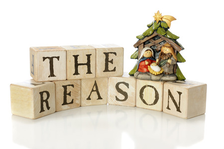 Rustic alphabet blocks arranged to say, The Reason, with a small nativity scene (Mary, Joseph and Jesus only) to demonstrate that reason for the season.  On a white background.  Stock Photo