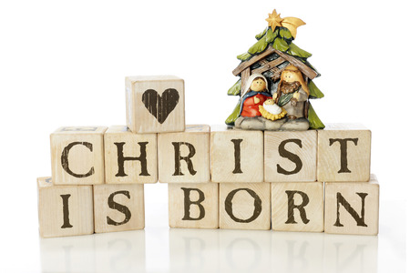 baby jesus: Rustic alphabet blocks arranged to say, Christ is born.  Theyre topped with a heart-block and a small nativity scene with Mary, Joseph and baby Jesus.  On a white background. Stock Photo