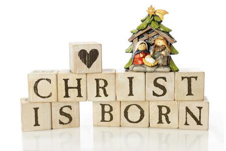 """geburt jesu: Rustikale Alphabet Bl�cke angeordnet, zu sagen: """"Christus ist geboren."""" Sie sind mit einer Herz-Block und eine kleine Krippe mit Maria, Joseph und dem Jesuskind gekr�nt. Auf einem wei�en Hintergrund."""