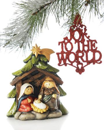 """장식 말하는 크리스마스 트리의 분기 아래 작은 출생 장면, 인근에 매달려 """"세계에 기쁨"""". 흰색 배경에."""