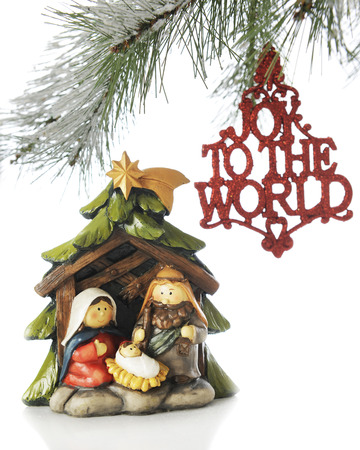 A small nativity scene under the branches of a Christmas tree with an ornament saying, Joy to the World hanging nearby.  On a white background. Stock Photo